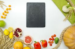Ortaggi freschi, frutta, tagliere nero su fondo bianco, vista superiore Fotografia Stock