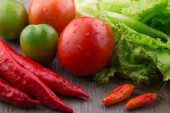 Ortaggi freschi: i peperoncini rossi rossi, uccelli osservano i peperoncini rossi, la lattuga, il pomodoro rosso ed il pomodoro v Immagine Stock Libera da Diritti