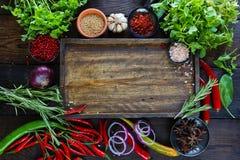 Ortaggi freschi, spezie ed erbe sulla tavola di legno e sul tagliere vuoto Fotografia Stock Libera da Diritti