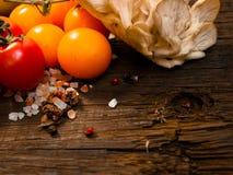 Ortaggi freschi su una tavola di legno strutturata con luce solare Luce calda e strutture di legno Pomodori rossi con le erbe Fotografie Stock