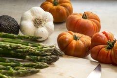 Ortaggi freschi sulla tavola, pomodori, aglio, asparago, avocado Fotografia Stock
