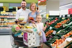 Ortaggi freschi vari di compera della famiglia in supermercato Immagine Stock