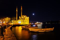 Ortakoy Mosque and embankment with swinging boats on background of Bosphorus Bridge at night