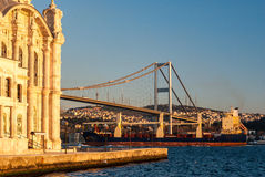 The Ortakoy Mosque in Istanbul. With the bridge across the Bosphorus and a containership in the background Stock Images