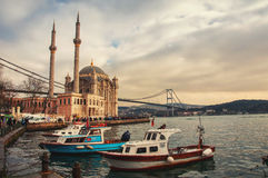 Ortakoy Mosque in Istanbul. ISTANBUL, TURKEY - DECEMBER 14, 2014: People outside the Ortakoy mosque. It was  built in Neo-baroque style. Bosphorus bridge at the Royalty Free Stock Image