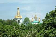 Orthodox churches peek out from behind the trees in Kyiv, Ukraine Royalty Free Stock Images