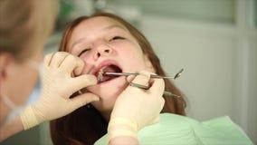 Orthodon kontrollerar tänderna av en tonåring som har kommit till kliniken för behandling stock video