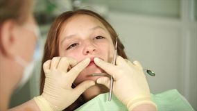 Orthodon kontrollerar tänderna av en tonåring som har kommit till kliniken för behandling lager videofilmer