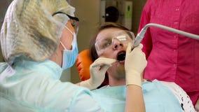 Orthodont heelt de tanden van een patiënt die voor de mondholte is komen geven stock video
