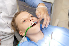 At the orthodontist. Young girl at the orthodontist while gluing the orthodontic brackets Stock Photography