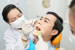 Orthodontist checking teeth. Professional orthodontist checking teeth of male patient stock images
