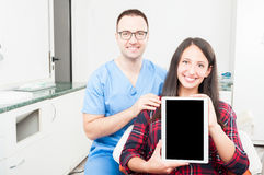 Orthodontist and patient holding tablet and smiling. As being friendly and trustworthy Royalty Free Stock Photos