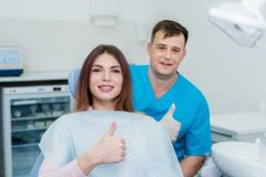 Doctor orthodontist posing on camera with her beautiful patient. Orthodontist posing on camera with her beautiful patient Royalty Free Stock Photo