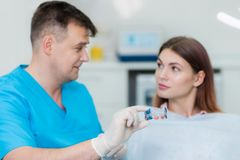 Orthodontist will explain to the patient how the plate aligns the teeth. Doctor orthodontist explain to the patient how the plate aligns the teeth Royalty Free Stock Photo