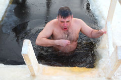 Orthodox believer takes a dip in ice cold water. Antoniyevo-Dymsky monastery, the Leningrad region, near St. Petersburg, Russia,- 19 January 2013. A Russian Stock Photos