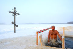 Orthodox believer takes a dip in ice cold water. Antoniyevo-Dymsky monastery, the Leningrad region, near St. Petersburg, Russia,- 19 January 2013. A Russian Royalty Free Stock Images
