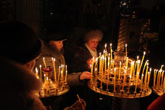Orthodox believers light candles in Pskov, Russia. PSKOV, RUSSIA - JANUARY 18, 2011: Orthodox believers light candles during the Epiphany evening service in the royalty free stock photography