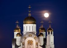 Orthodox cathedral with golden domes and full moon. Behind Stock Photo