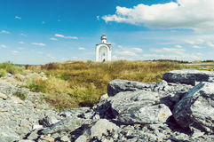 Orthodox chapel white with a transparent facade on the background of the panorama of the sea and blue sky in a field Stock Photo