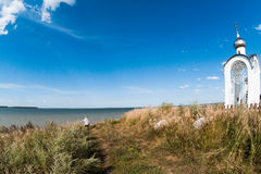 Orthodox chapel white with a transparent facade on the background of the panorama of the sea and blue sky in a field Royalty Free Stock Images