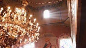 Orthodox, Christendom, kerk De lichtstraal glanst over oude gondelkroonluchter met kaarsen die vanaf de bovenkant hangen van stock videobeelden