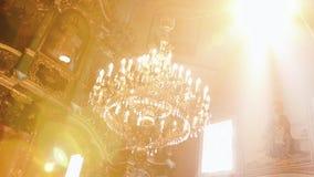 Orthodox, Christendom, kerk De lichtstraal glanst over oude gondelkroonluchter met kaarsen die vanaf de bovenkant hangen van stock video