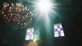 Orthodox, Christendom, kerk De lichtstraal glanst over oude gondelkroonluchter met kaarsen die vanaf de bovenkant hangen van stock footage