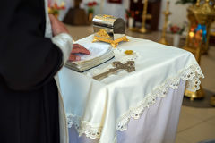 Orthodox christian priest performs rite. Close up orthodox priest in black clothes standing next to a rostrum with cross and bible performing religious rite Stock Image