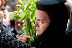 Orthodox Christians mark Good Friday in Jerusalem. JERUSALEM - APRIL 13: A Russian Orthodox nun carries a bouquet of Easter lilies along the Via Dolorosa in Royalty Free Stock Photos