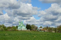 Orthodox church against the blue sky. Pair of pigeons are sitting on a green fence Stock Photo