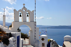 Orthodox church bells, Mediterranean sea and Santorini caldera  Greece. Horizontal view to the enterance to orthodox church on Thera island in bright sunny Royalty Free Stock Photos