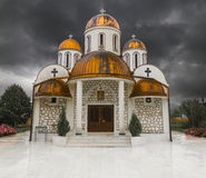 Orthodox church with copper roof. Small white orthodox church with copper clad cupola roof in front of a dramatic thunder storm royalty free stock photo