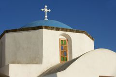 Orthodox church dome and cross in Pyrgos, Santorini, Greece. Stock Photos