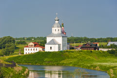 Orthodox church on the green lawn near the river. The city of Suzdal Russia Royalty Free Stock Photo