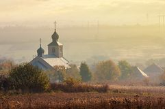 Orthodox church on a hill. Above the foggy rural valley at sunrise. lovely countryside scenery in autumn Royalty Free Stock Photography