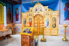 Orthodox church from the inside. Burning wax candles in front of icons and frescoes. Christian religion. Holy Hand, Russia - June 24, 2017: Orthodox church from Royalty Free Stock Images