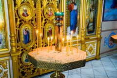 Orthodox church from the inside. Burning wax candles in front of icons and frescoes. Christian religion. Holy Hand, Russia - June 24, 2017: Orthodox church from Stock Photo
