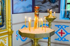 Orthodox church from the inside. Burning wax candles in front of icons and frescoes. Christian religion. Holy Hand, Russia - June 24, 2017: Orthodox church from Stock Photos