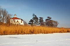Orthodox church near a frozen lake in the sunset Stock Photo