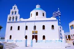 Orthodox church in Oia - Santorini. Church on Santorini Island - Oia - Greece. Blue sky, white church, bells towe and greek flag Royalty Free Stock Photos