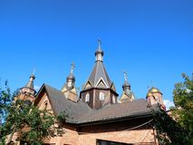 Orthodox church roof in summer. Triangular  black dark wood cupola with crosses of an orthodox temple against the background of bright blue sky, Temple St. Peter Stock Photography