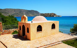 Orthodox Church and Spinalonga island at background Royalty Free Stock Image