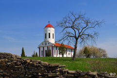 Orthodox Church. In the village of shaving near Leskovac is located on a wide green plateau church portals've painted in white with a bright red tower bell Royalty Free Stock Photography