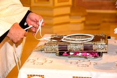 Orthodox Cristian priest hands and wedding crowns decorated on a. Orthodox Christian priest hands and wedding crowns decorated on a gospel preparing for ceremony Stock Images