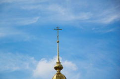 Orthodox cross on a dome of church. Orthodox cross on a gold dome of church against the sky Stock Photos