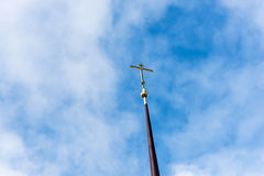 Orthodox cross on a long spire against the blue sky. Royalty Free Stock Images