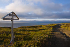 Orthodox cross at sunset over the Arctic Ocean Royalty Free Stock Photo