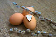 Orthodox Easter. Eggs and willow with heart on canvas. stock photo