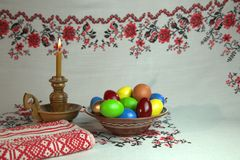 Orthodox Easter. On a table covered with a tablecloth with ornaments worth plate with colored eggs. Nearby stands a candle in a candlestick. White background Stock Photography