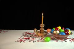 Orthodox Easter. On the table is a plate with colored eggs. Nearby stands a candle in a candlestick. Black background. Under the alpha channel Stock Images